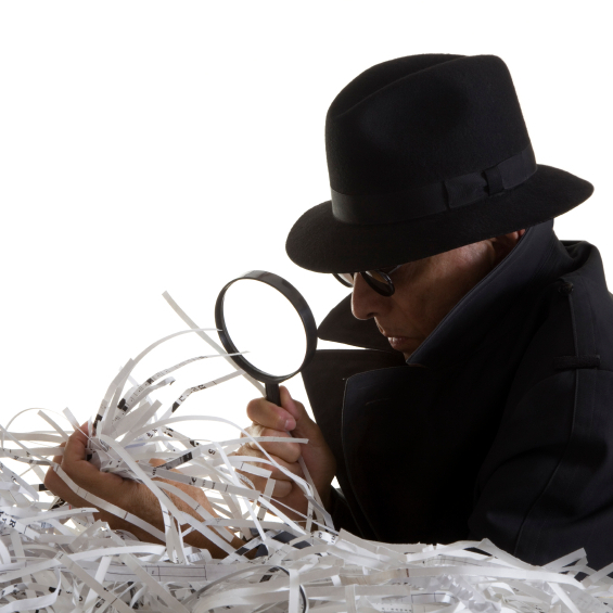 A thief sifts and examines shredded documents