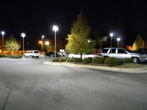 A parking lot at night with cars and lightposts